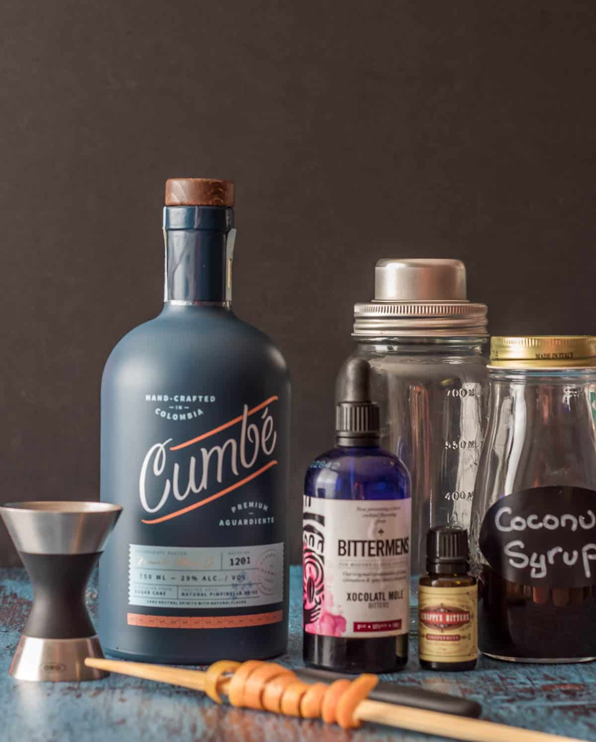 Ingredients for an aguardiente cocktail: Cumbe aguardiente, mole bitters, grapefruit bitters, coconut syrup, grapefruit twist.