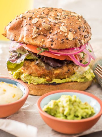 A healthy Mexican turkey burger on a whole grain bun, a bowl of mashed avocado, and a bowl of blood orange aioli.
