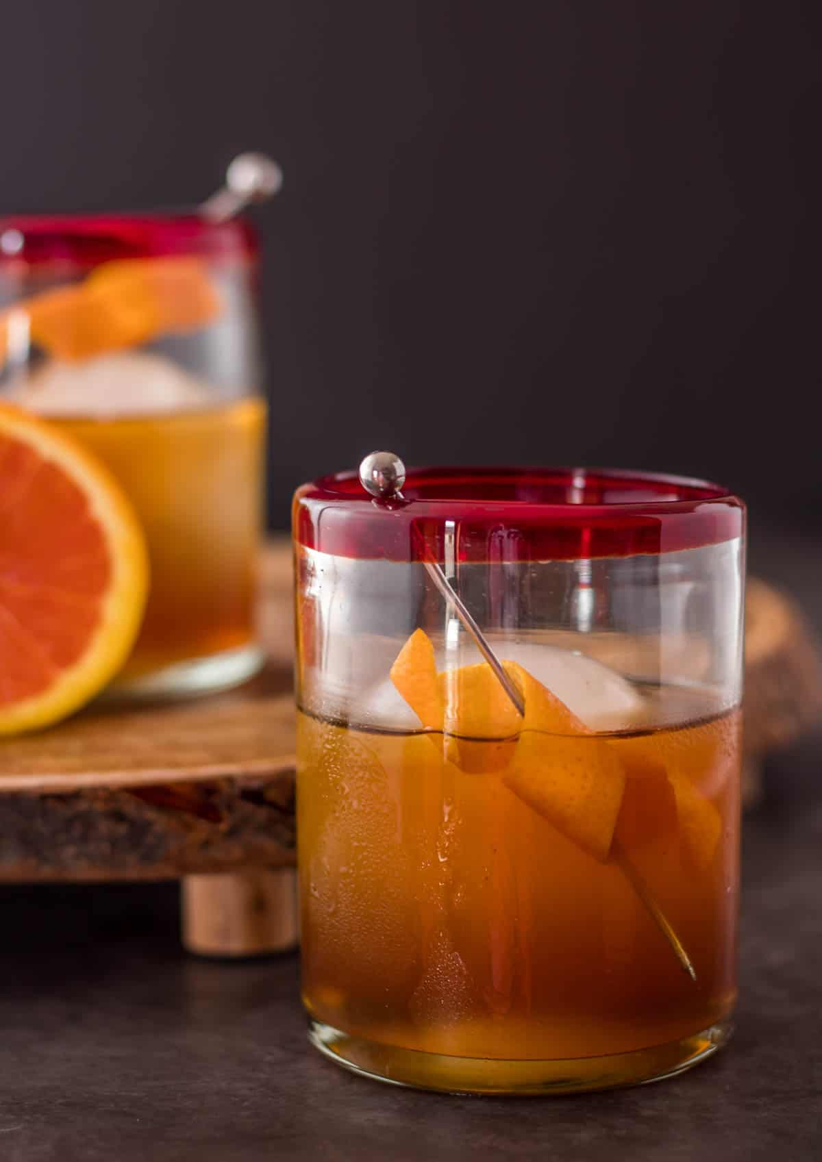 Two orange pomegranate manhattans on a wood board with a cara cara orange.