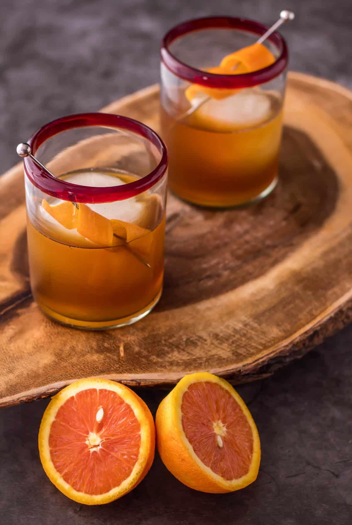 A burl wood cutting board orange pomegranate Manhattans in rocks glasses, garnished with a spiralized orange peel.