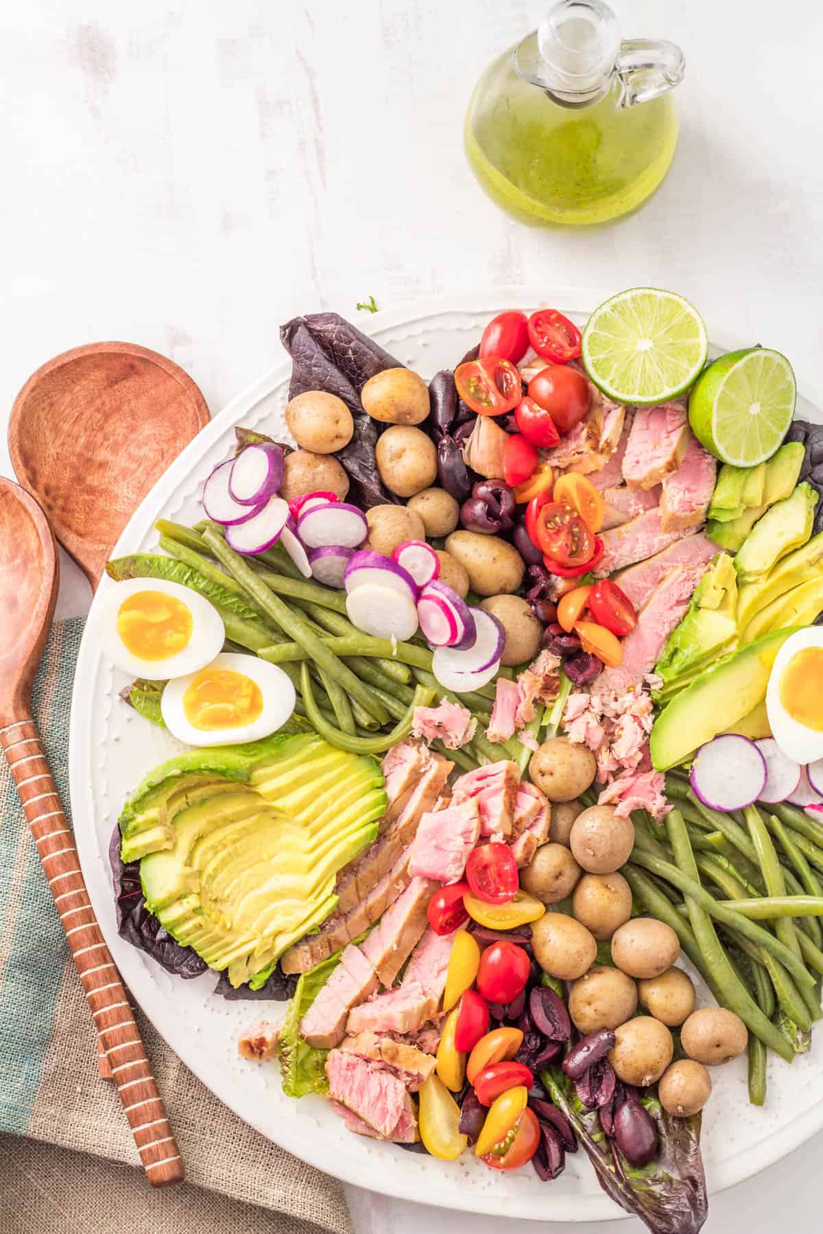 A large white platter with seared tuna, tomatoes, potatoes, green beans, radishes, soft boiled eggs, olives.