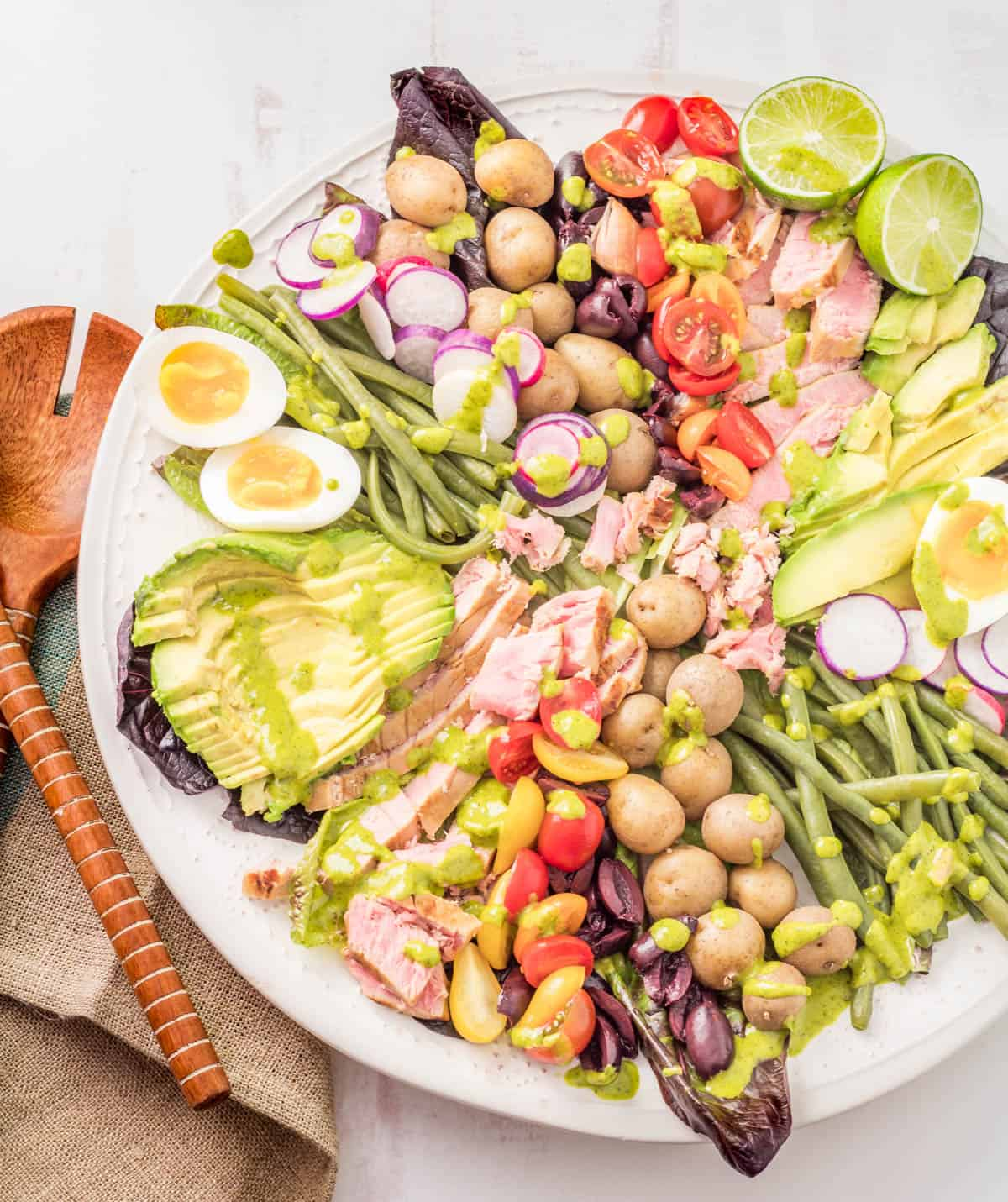 The completed Nicoise salad on a white platter with wood salad utensils and a beige linen napkin.