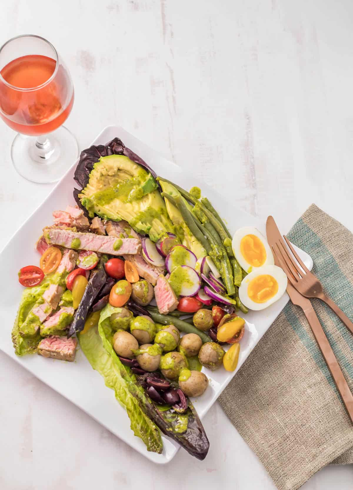 A square white plate with Peruvian-inspired Nicoise Salad, copper flatware, beige linen napkin, and a glase of rosé.