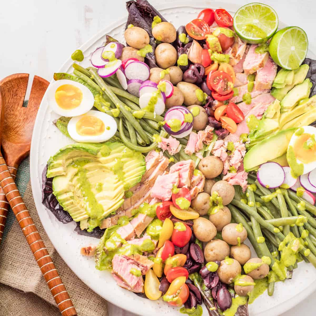 A close up of a white ceramic platter with Peruvian-inspired Nicoise Salad drizzled with the cilantro lime dressing and wood salad utensils.