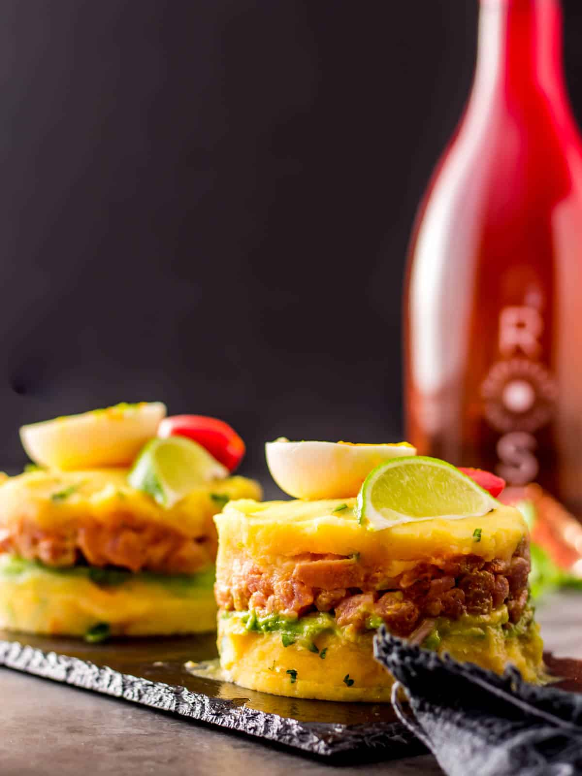2 raw tuna causa stacks on a slate tray with a bottle of rose.