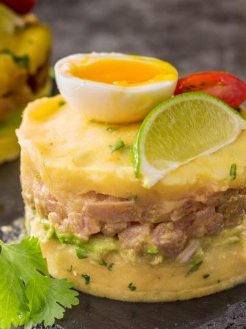 A close up of 1 raw tuna tartare causa garnished with egg, lime wedge, and tomato on top of a slate plate.