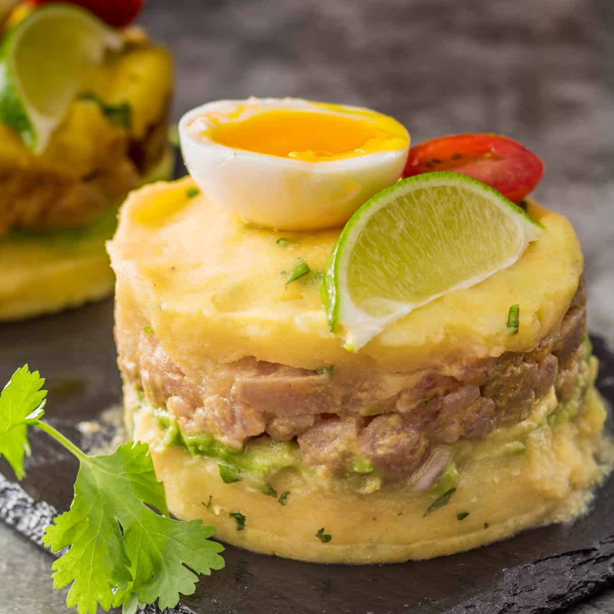 A close up of a tuna causa with a boiled egg, lime wedge, and tomato.