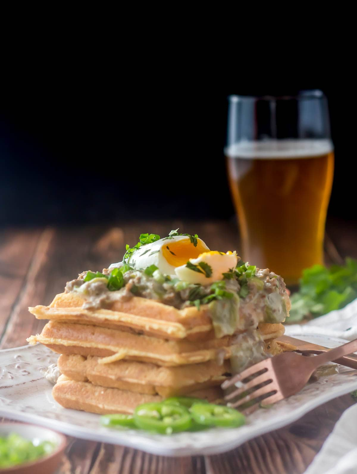 Waffles with green chile sausage gravy, a poached egg with broken yolk, and copper flatware.