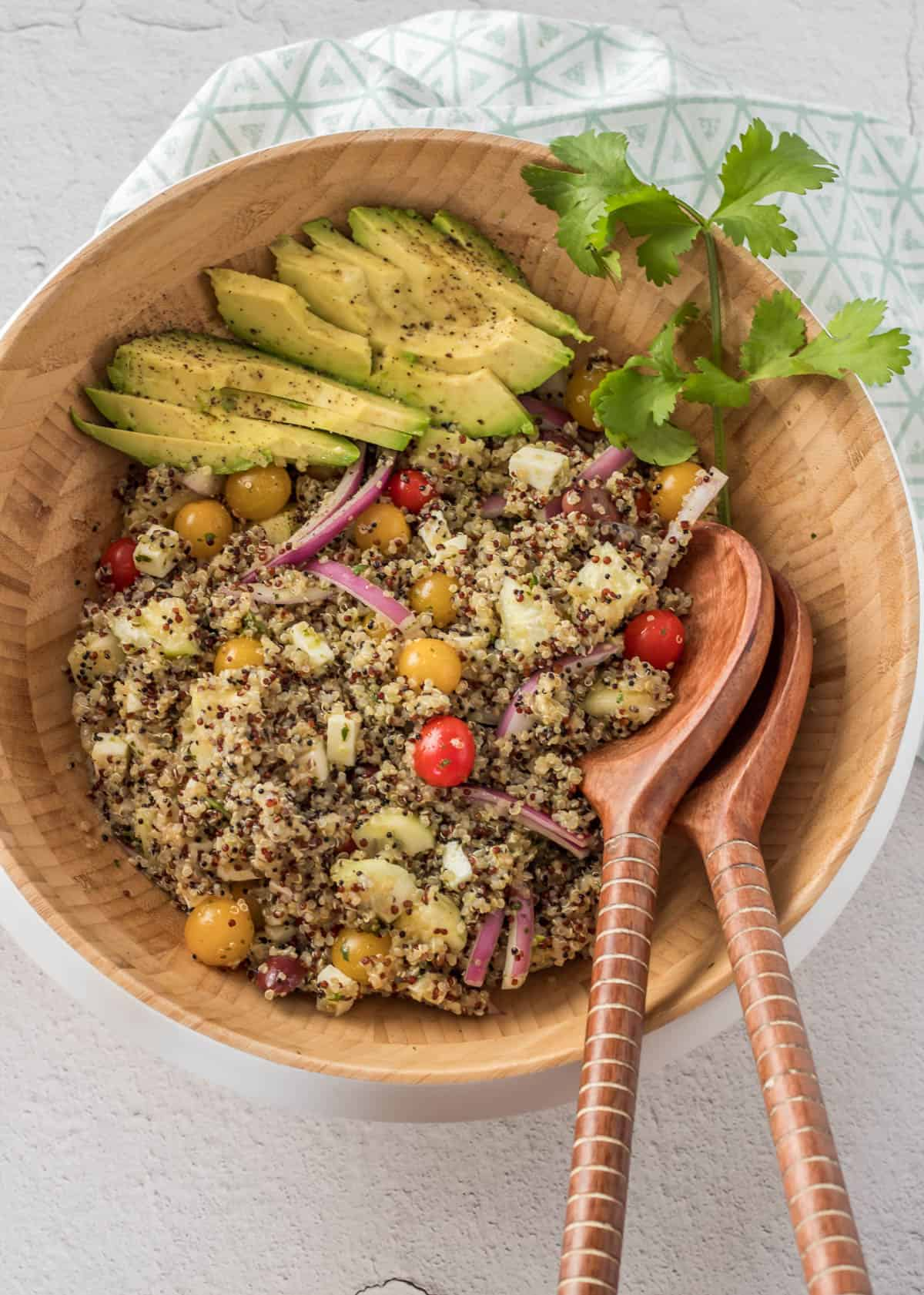 A wood salad bowl with healthy Peruvian quinoa salad, sliced avocado, and a sprig of cilantro with wood salad utensils and print napkin.