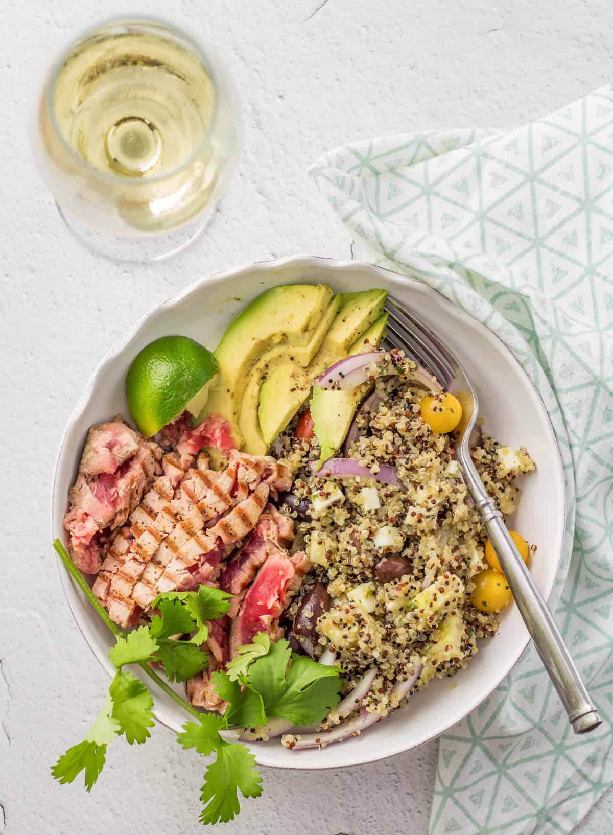 The Peruvian quinoa salad served with seared ahi tuna and sliced avocado in a white ceramic bowl and a glass of wine.