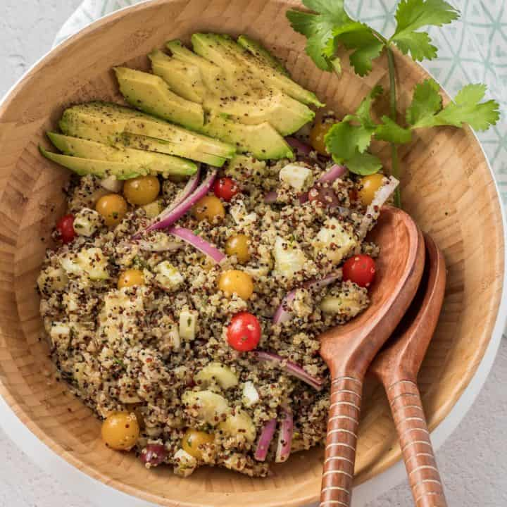 A wood salad bowl with Peruvian quinoa salad, sliced avocados and wood salad utensils.