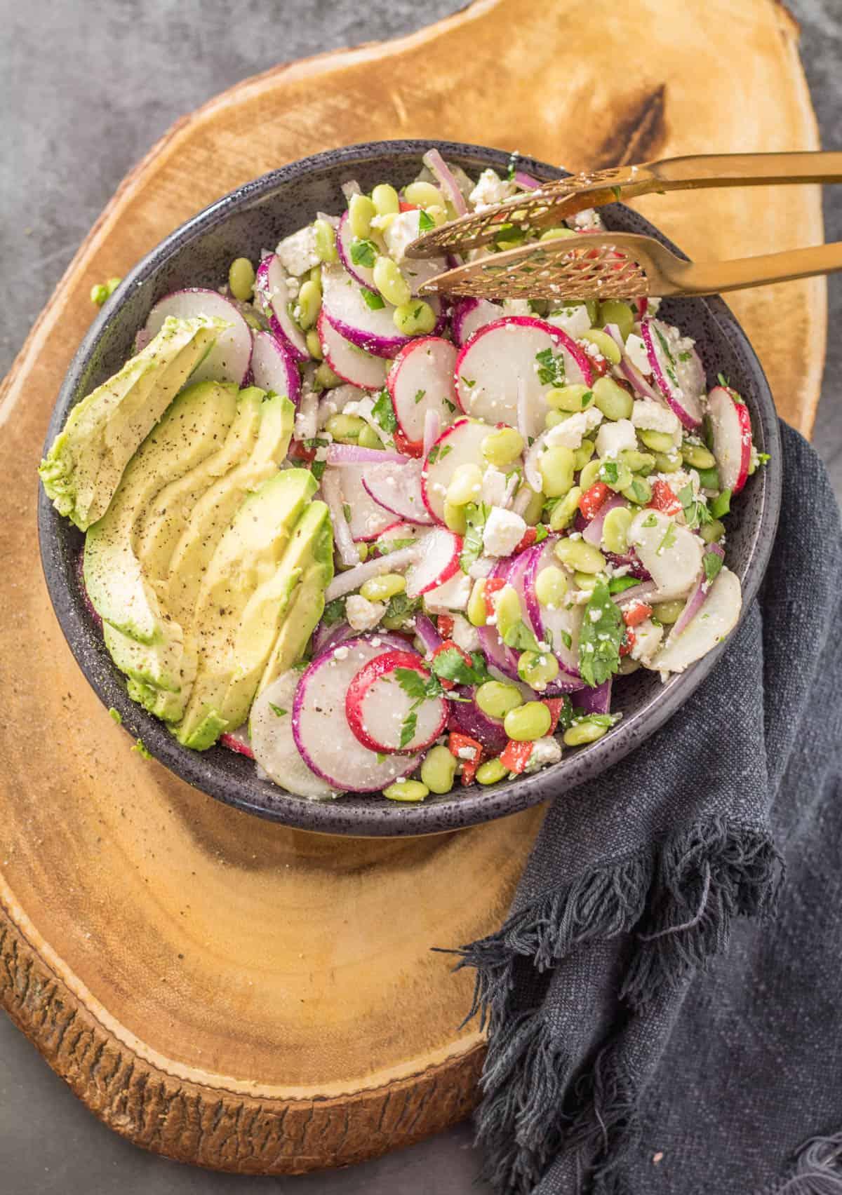 A black stoneware bowl of sarsa salad and sliced avocado with copper tongs and grey napkin.