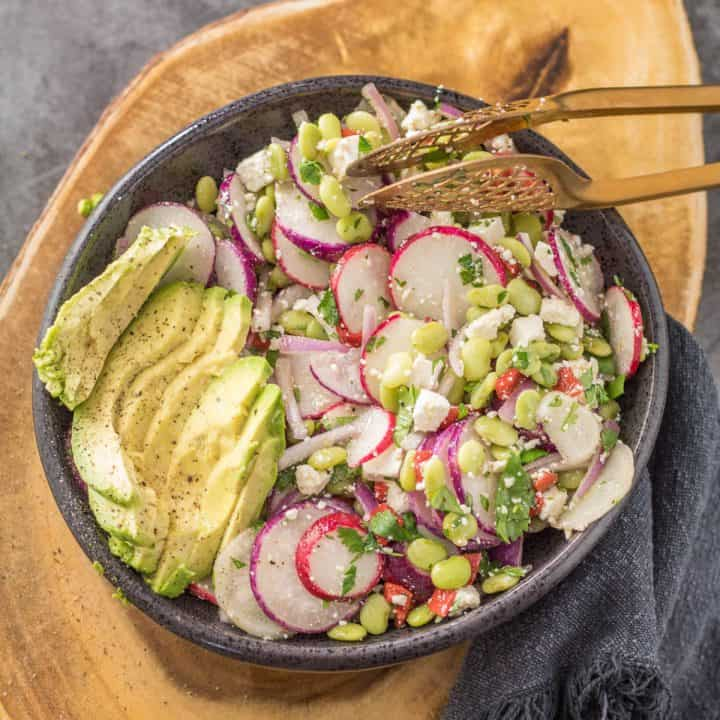 A black stoneware bowl on a wood cutting board with healthy Peruvian sarsa salad and sliced avocado.