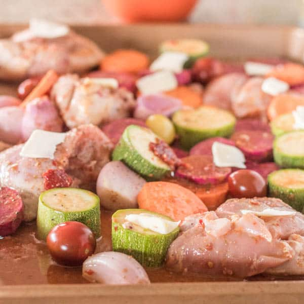 A copper sheet pan with the prepared chicken thighs and veggies in the citrus-chipotle glaze just before roasting.