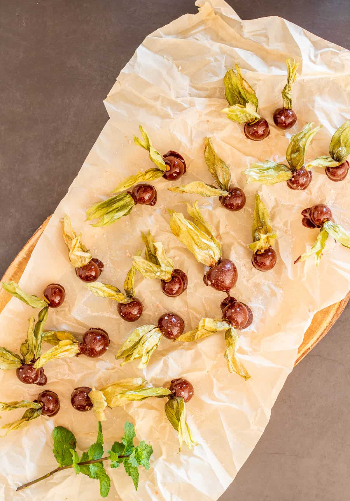 Parchment on a baking sheet with chocolate covered goldenberries.