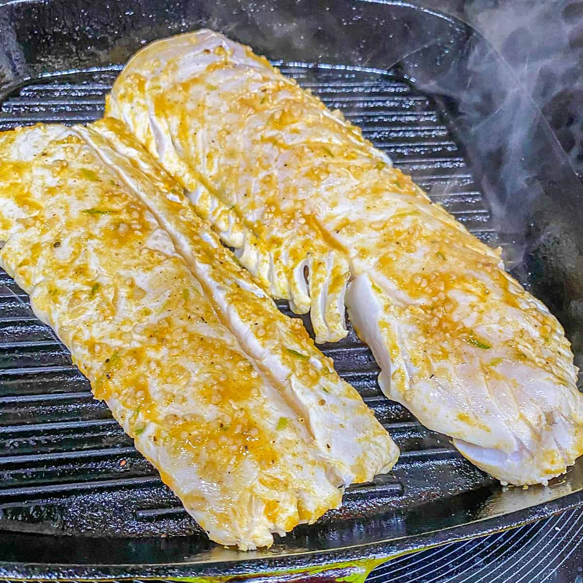 A cast iron grill pan with 2 marinated fish fillets.