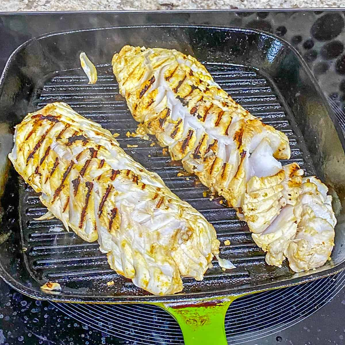 Two fish fillets turned after cooking on the first side with grill marks.