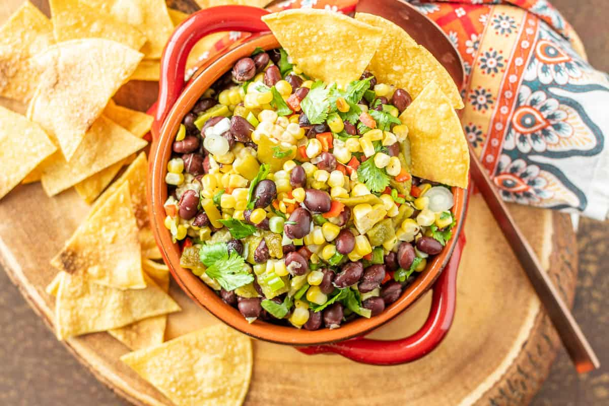 A close up of the grilled corn and black bean salsa with Hatch chile in a 2 handled red ceramic bowl with tortilla chips.