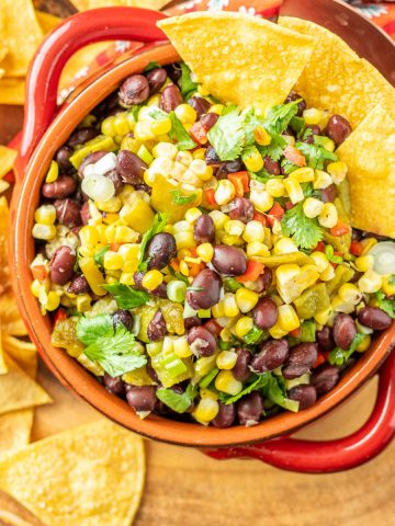 A red stoneware bowl with grilled corn and black bean salad alongside air fryer tortilla chips.