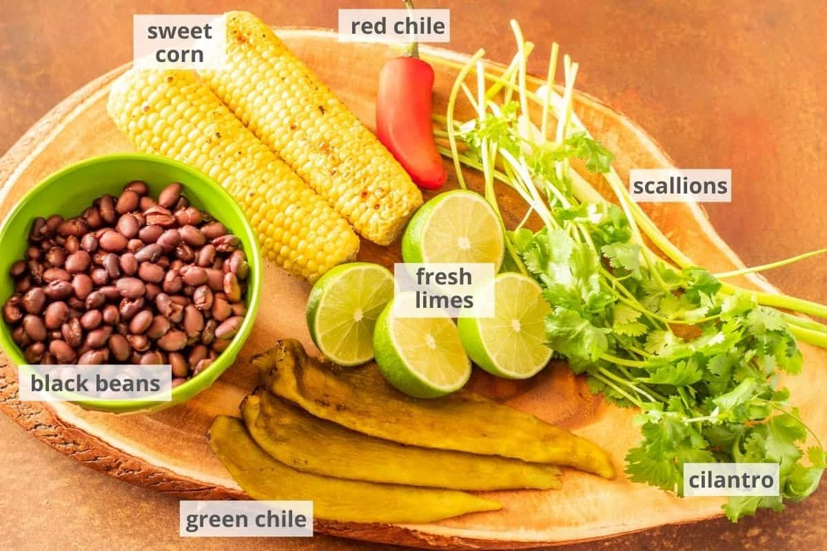 A wood cutting board with black beans, grilled corn, red jalapeno, cilantro, fresh limes, and Hatch green chile.