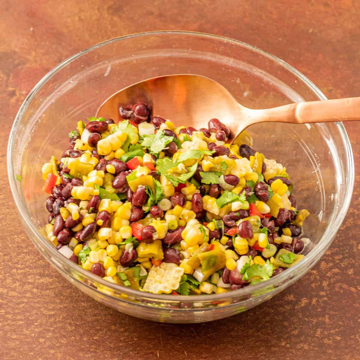 The clear glass bowl with the beans, corn, chiles, cilantro, and scallions mixed together with fresh lime juice.