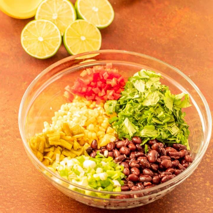 All of the salsa ingredients in a clear glass bowl with sliced limes before mixing.