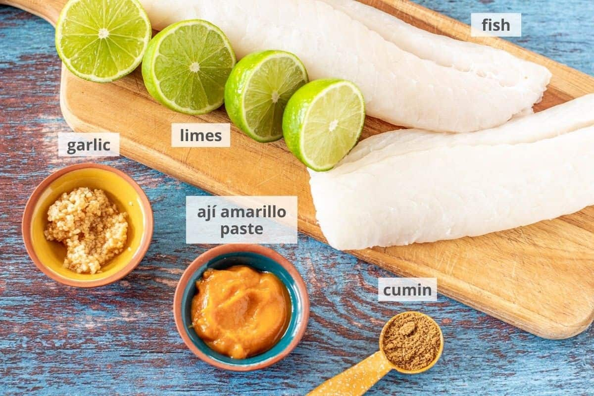 A wood cutting board with fish tacos ingredients: Cod fillets, cumin, aji amarillo paste, garlic, and limes.