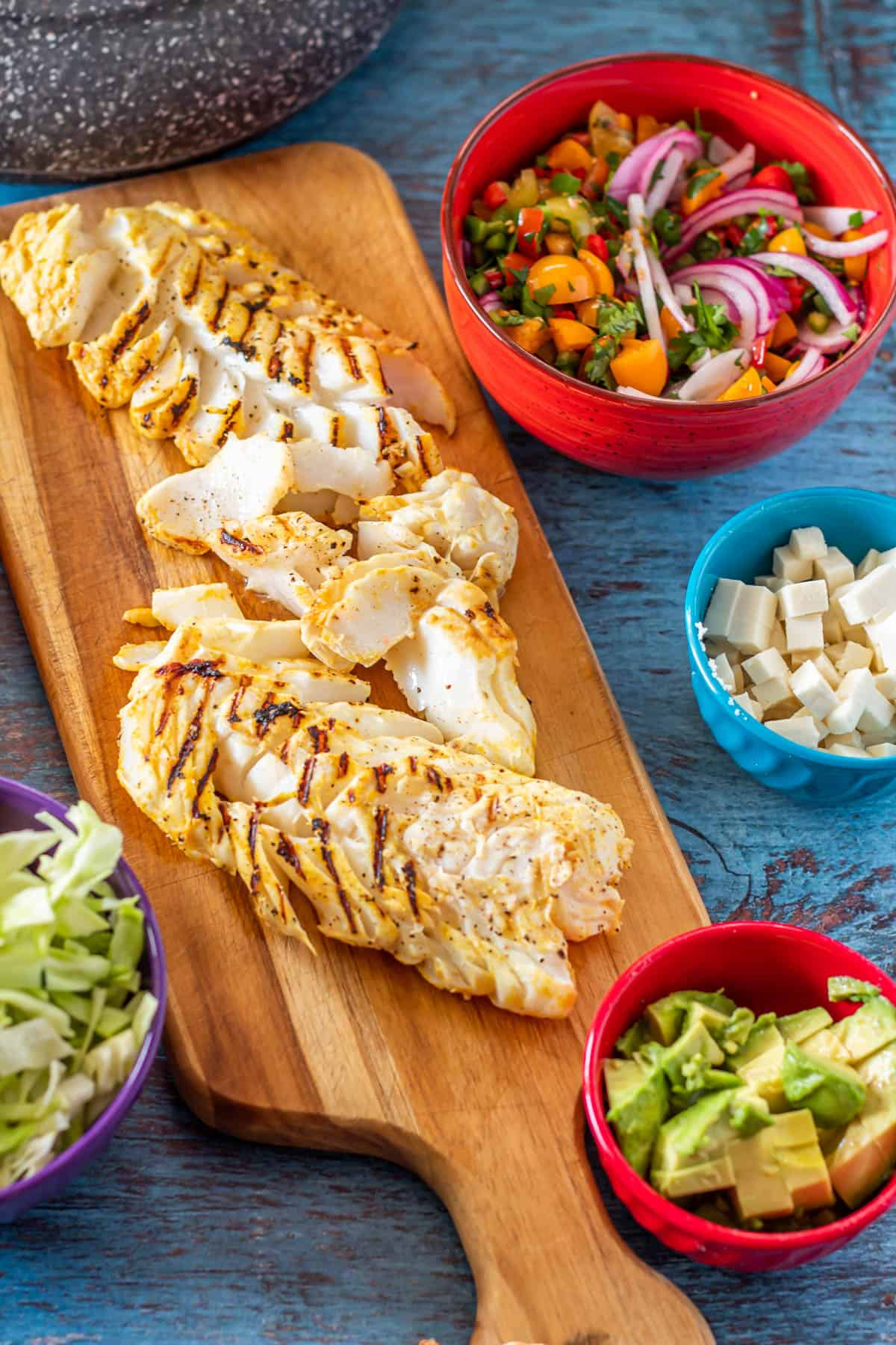 All of the ingredients for Peruvian-inspired fish tacos: Prepared fish, goldenberry pico de gallo, queso fresco, avocado, shredded cabbage!