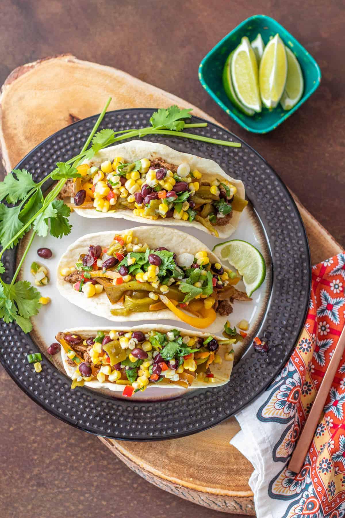 A bronze ceramic plate with 3 pork fajita tacos with corn and black bean salsa.