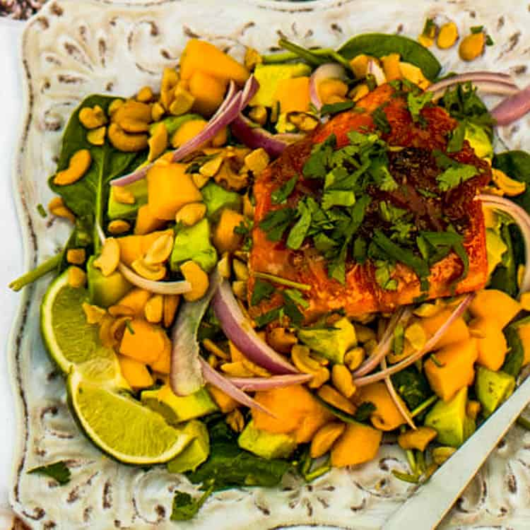 A close up bird's eye view of the ginger-glazed salmon atop the spinach salad with mango, avocado, cashews, red onion, and lime wedges.