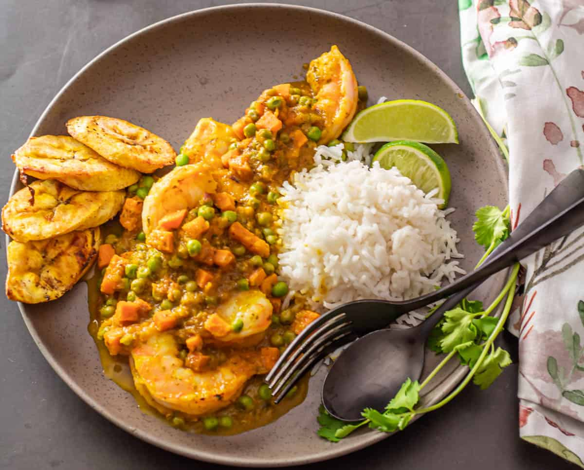 A grey plate with shrimp in goldenberry sauce, a scoop of rice, air fryer plantains, lime wedges, and cilantro.