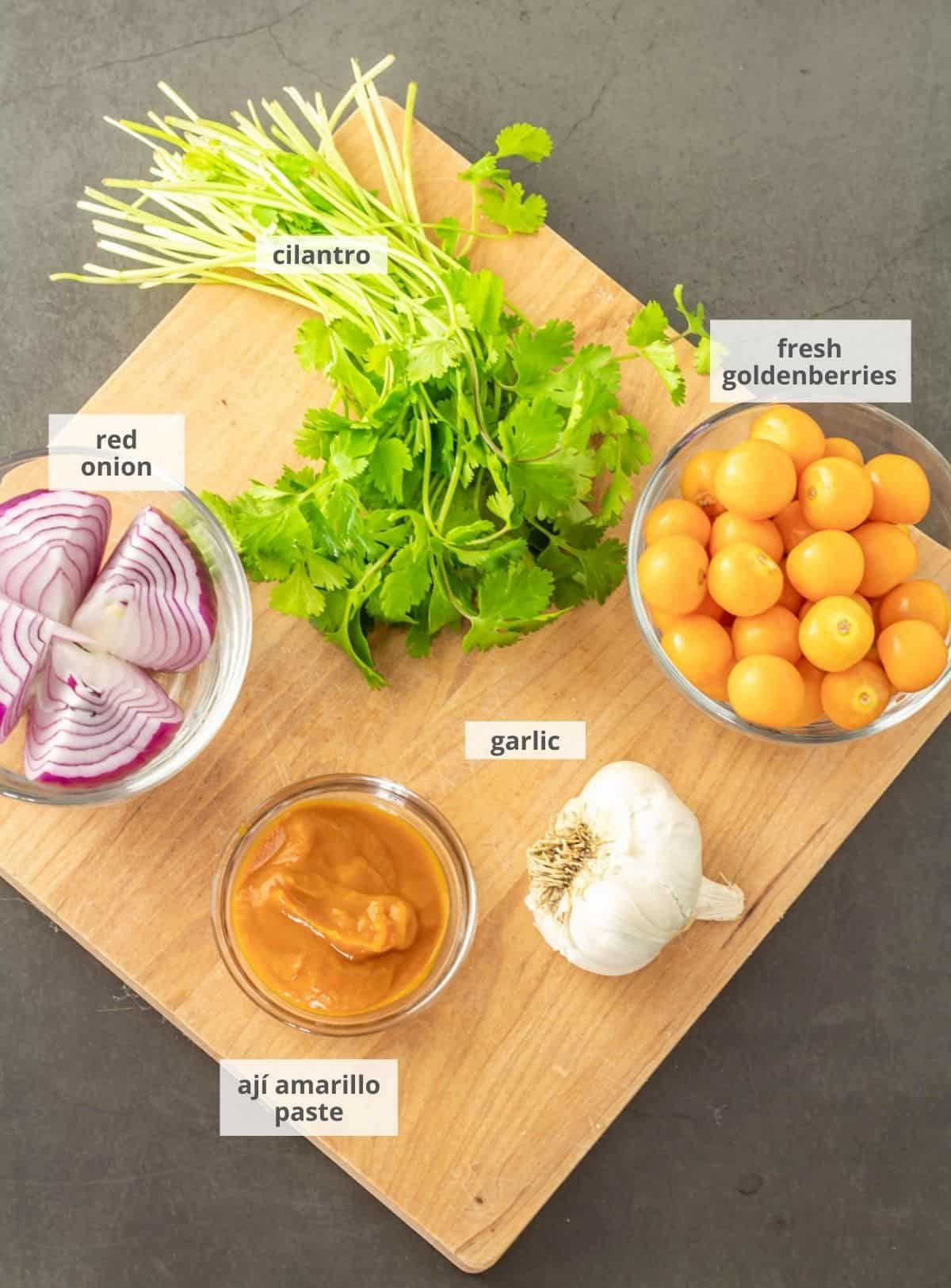 Ingredients for the roasted goldenberry sauce: Goldenberries, garlic, ají amarillo sauce, red onion, and cilantro on a wood cutting board.