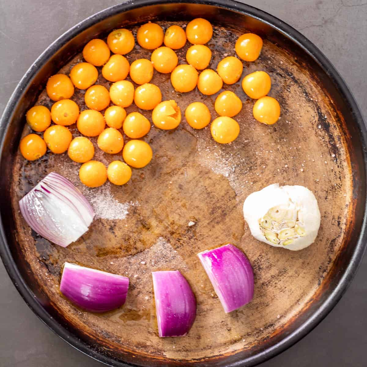 A clay baking dish with goldenberries, red onion, and garlic before roasting.