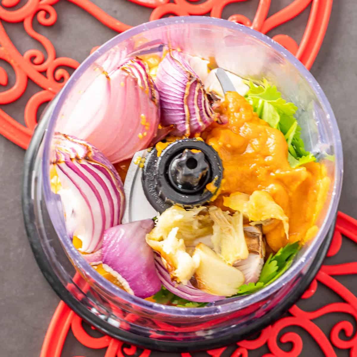 A small food processor with onion, aji amarillo paste, garlic, cilantro, and goldenberries.