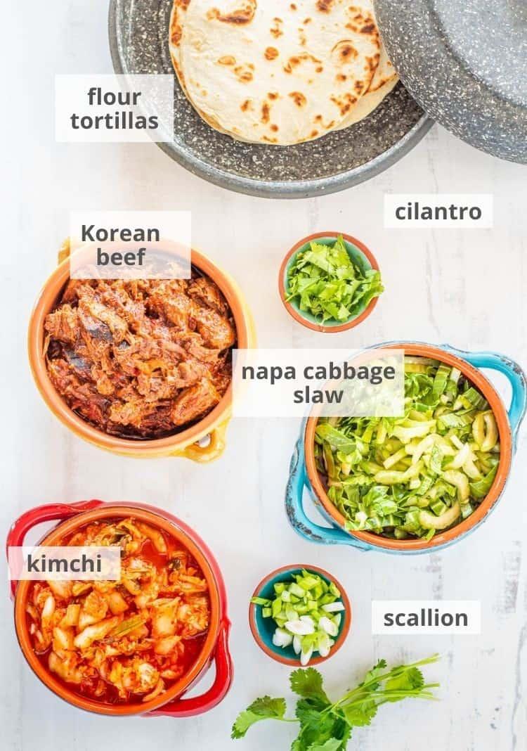 The taco ingredients ready to assemble: Korean beef, napa cabbage slaw, kimchi, flour tortillas.