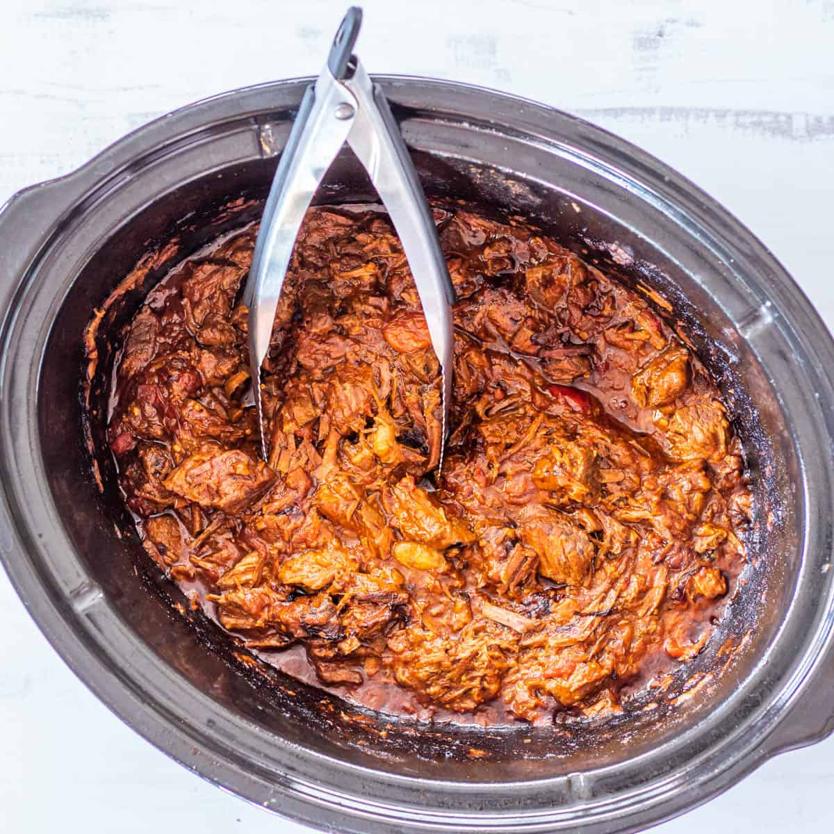 Slow-cooked and shredded Korean beef  in a black slow cooker with stainless steel tongs.