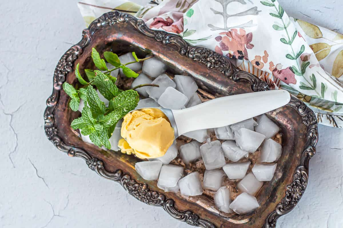 A silver tray full of ice with vegan passionfruit ice cream in a white ice cream scoop.
