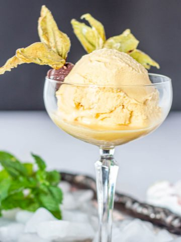 A coupe glass with vegan passionfruit ice cream on a silver tray with 2 chocolate covered goldenberries.