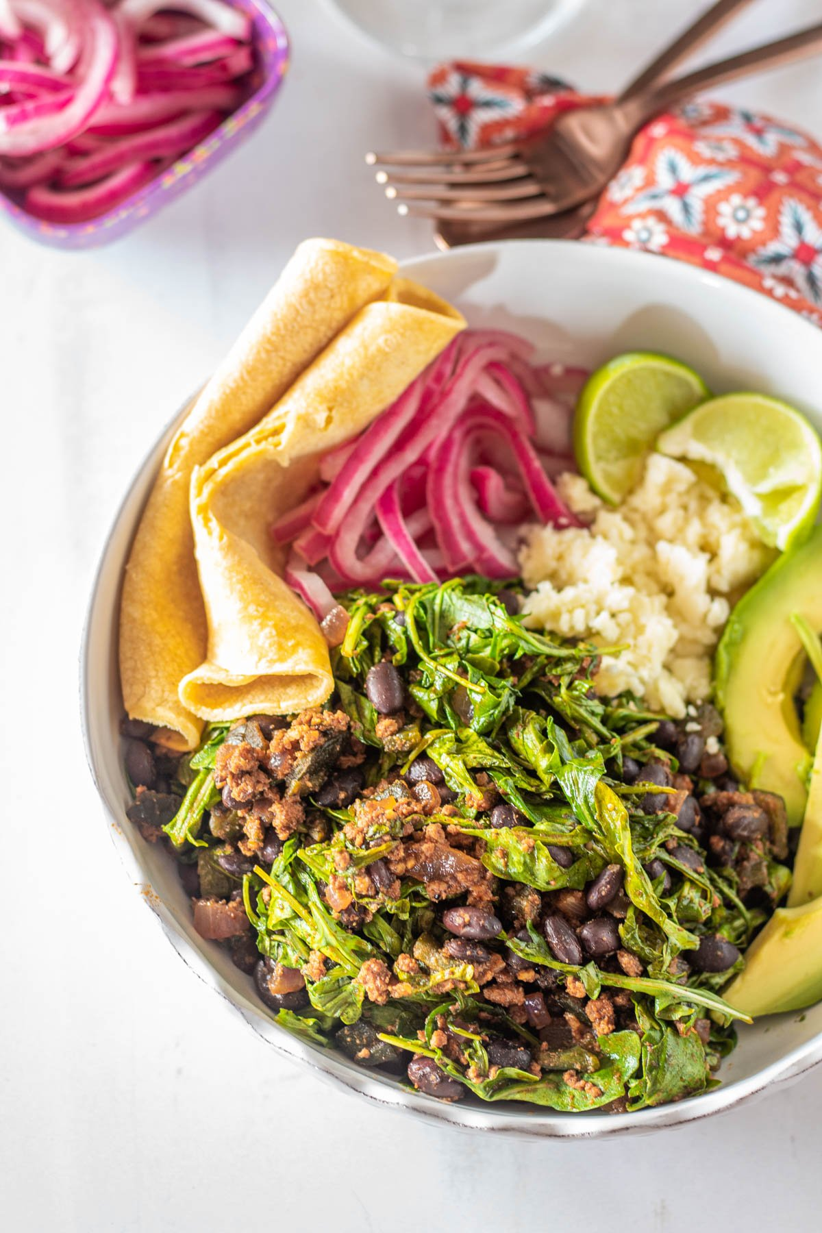 A white ceramic bowl with Mexican Black Beans Chorizo and Greens, avocado, pickled onions, crumbled cotija, lime wedges, and tortillas.