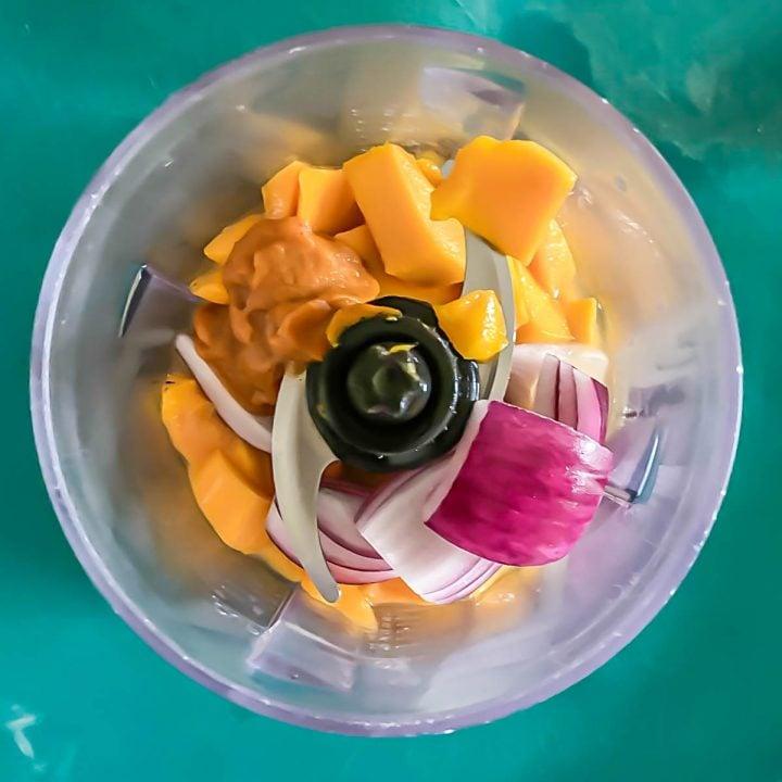Mango, shallot, and aji amarillo paste in a food processor for the mango sauce.