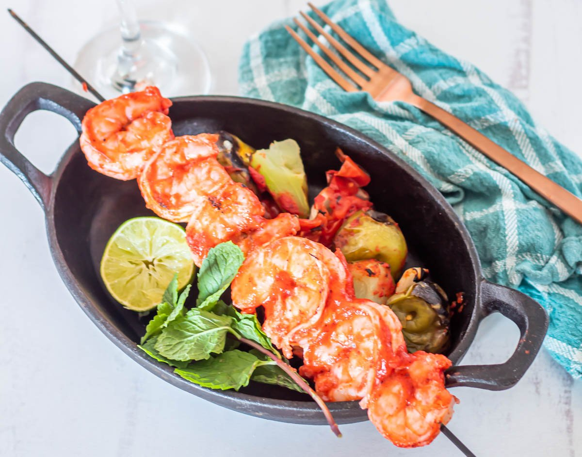 A skewer of achiote shrimp with grilled veggies, a lime half, and a mint sprig.
