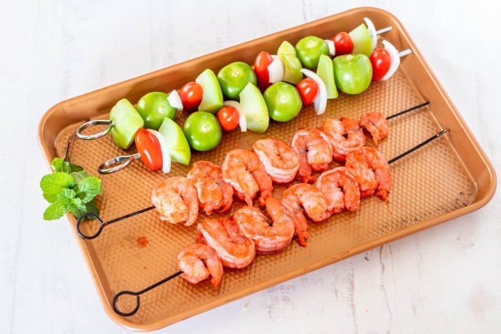 A copper baking tray with shrimp skewers and veggie skewers.