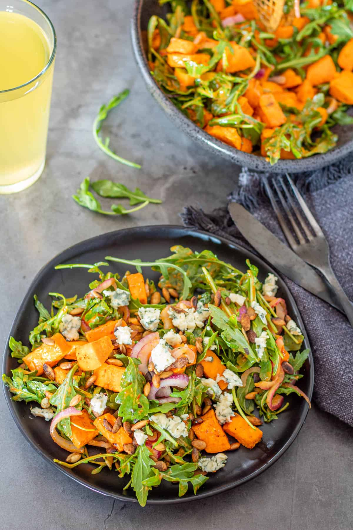 A plate of Mexican Sweet Potato Salad with Chipotle Vinaigrette combines healthy roasted sweet potatoes with peppery arugula and thin-sliced red onion with a zesty chipotle vinaigrette... optional bleu cheese and pepitas make this a spectacular vegetarian main dish salad or side dish with your mains! next to a large bowl of salad with flatware, grey napkin, and a beer.