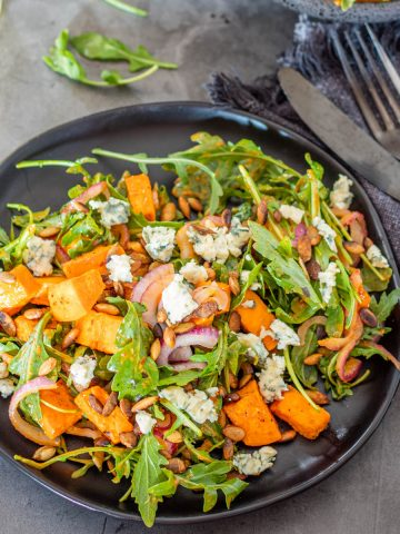 A black stoneware plate with sweet potato and arugula salad garnished with bleu cheese and toasted pepitas, black flatware, and a grey napkin.