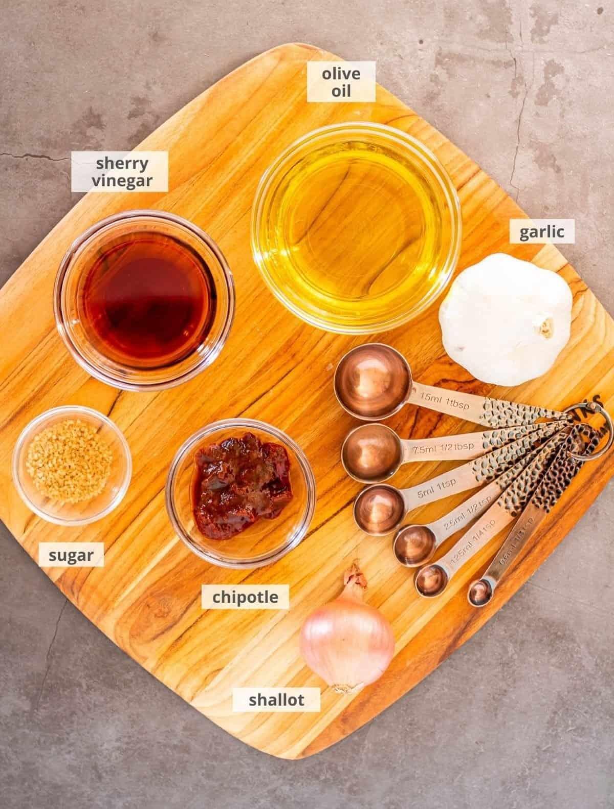 The ingredients for the chipotle vinaigrette: olive oil, garlic, shallot, chipotle, sugar, sherry vinegar.