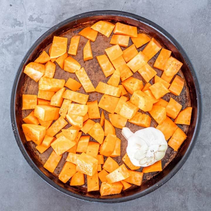 A stoneware roasting pan with diced sweet potatoes and a bulb of garlic before roasting.