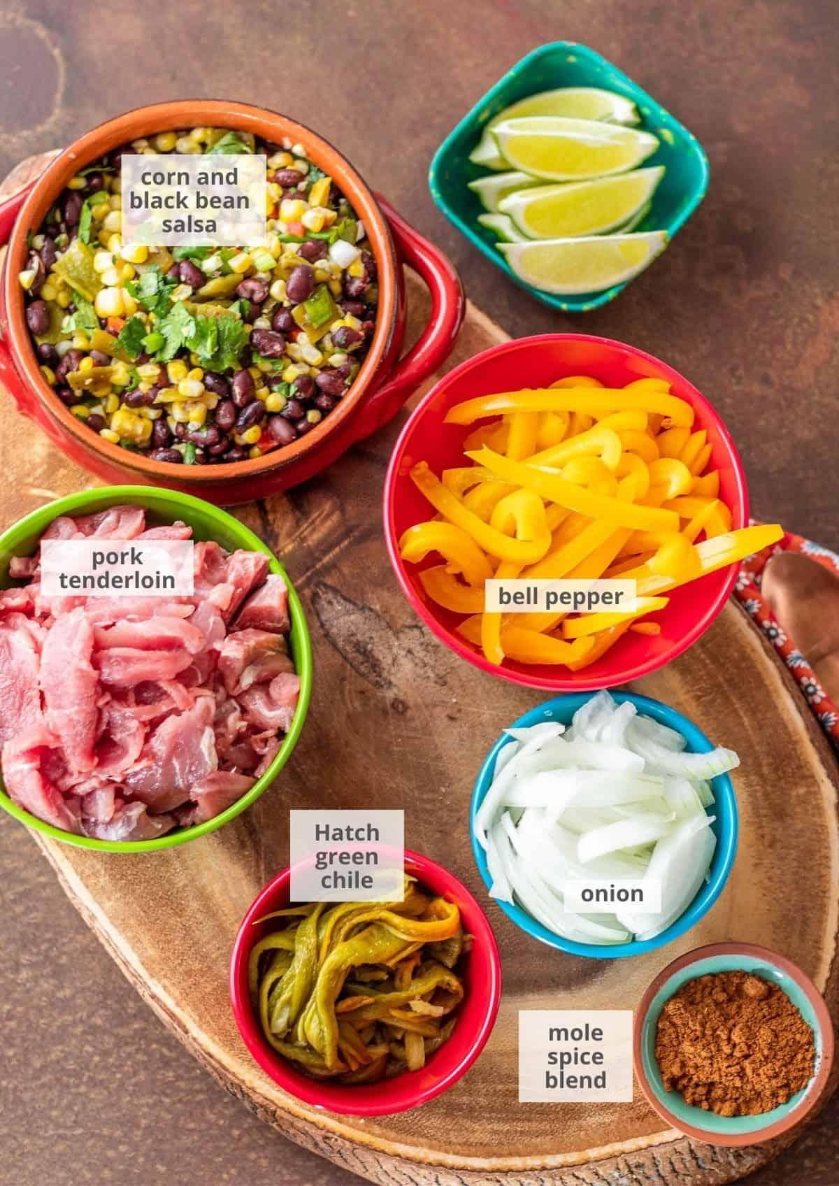 Ingredients for pork fajita tacos on a wood burl cutting board in bright prep bowls.