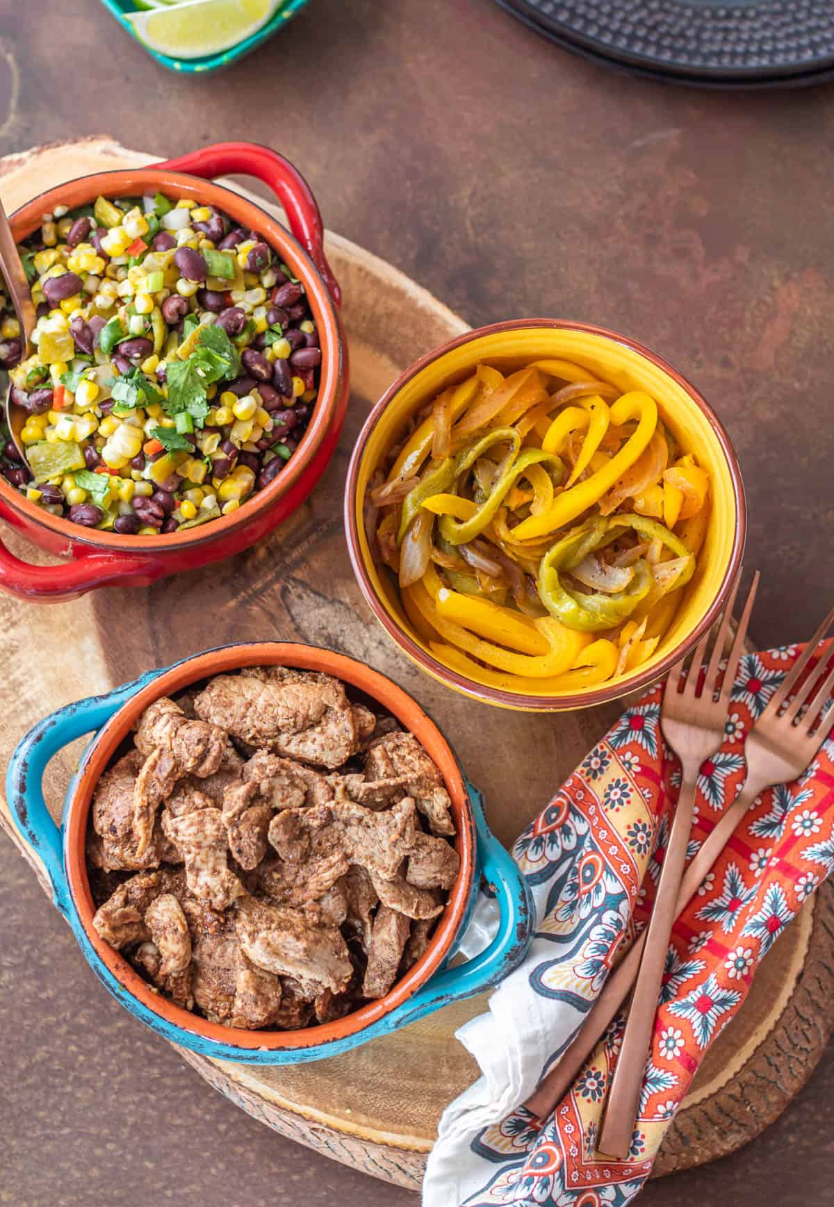 3 stoneware bowls with pork fajita taco ingredients - cooked pork tenderloin, green chile and pepper strips, and grilled corn and black bean salsa.