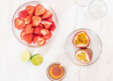 Halved strawberries, halved passionfruit, halved lime, and piloncillo syrup in glass prep bowls.
