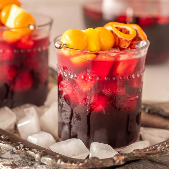 An antiqued silver tray with 2 glasses of Peruvian Sangria topped with fresh fruit garnish.